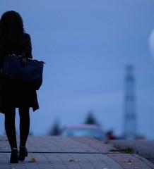 Woman walking home on dark bridge